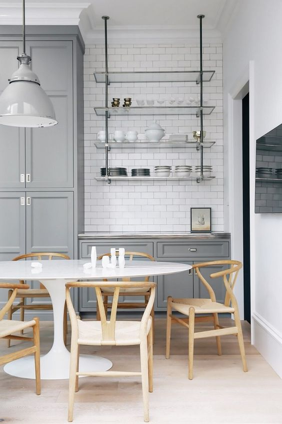Industrial kitchen with subway tile, gray cabinents, a large industrial light, and wishbone chairs: