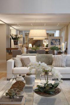 sala de esatr decorada no estilo contemporâneo, com sofá branco, almofadas em tons neutros, espelho grande atrás do sofá, vaso com flor branca em cima da mesa de centro de vidro transparente: