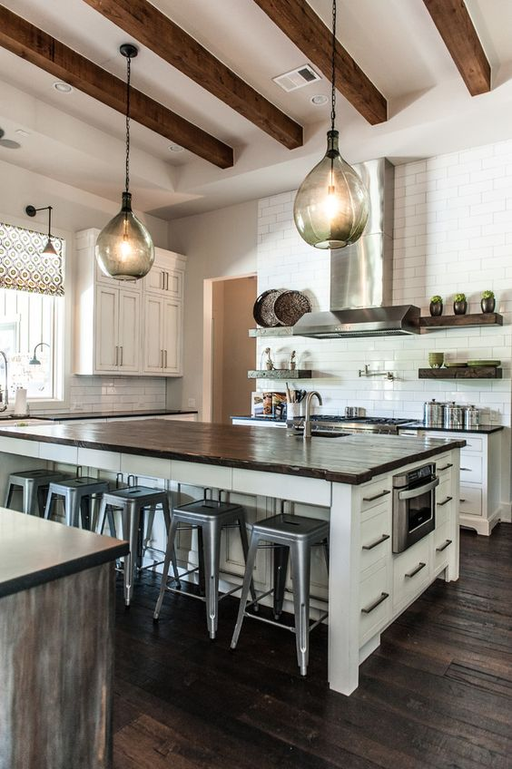 Kitchen with dark wood floors, exposed wood ceiling beams, large island with wood countertop, white cabinets, pendant lighting | Schroeder: