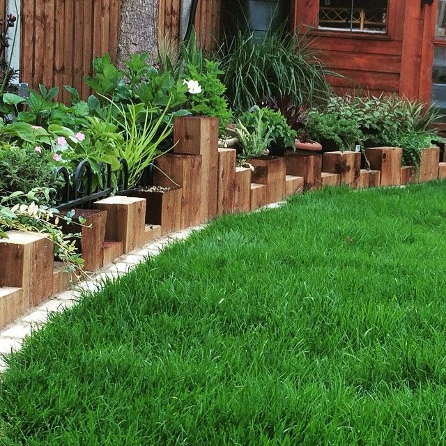 Vertical sleeper planting bed edging. Tomoco landscaping
