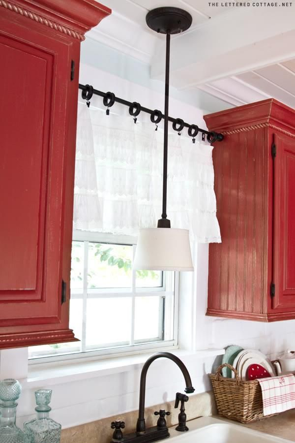 use a tension rod between two cupboards to hang a kitchen window curtain – change out your recessed light over the sink for a