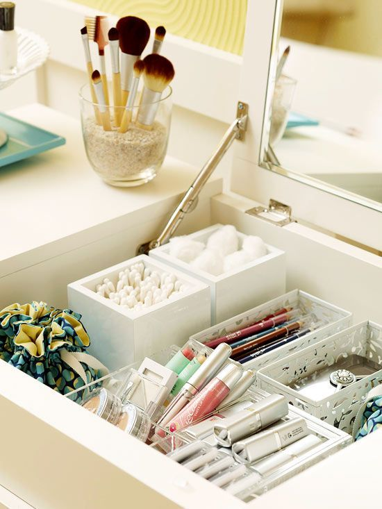 Organize a makeup and jewelry station with modular containers, use tine fabric sacs for jewelry, and fill a vase with sand to hold makeup brushes: