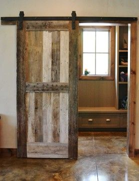 Sliding barnwood door to separate the mudroom from the rest of the home, custom made by Burchette.  Stained concrete flooring with