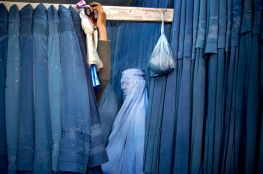 A woman waits in a changing room to try on a new burqa at a shop in Kabul, Afghanistan.