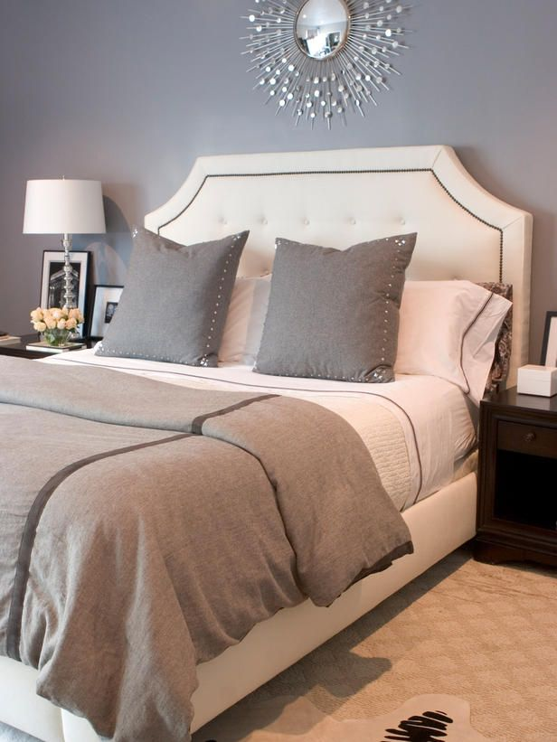 Guest Room – Glamorous Gray. A neutral, tufted and nail-studded headboard stands out against gray walls and bedding. Accessories are kept to a minimum, allowing the bed to take center