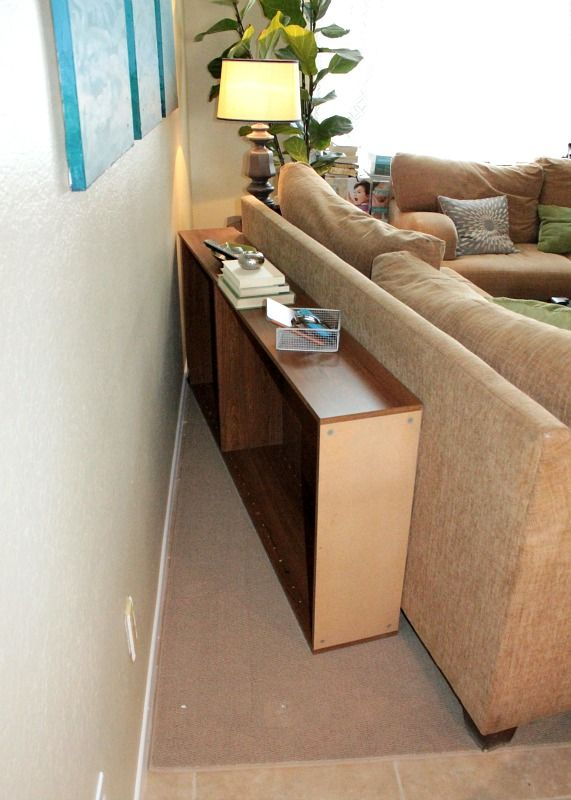 Upcycle a bookcase into a behind the couch table, then just push the case & couch up against the wall!