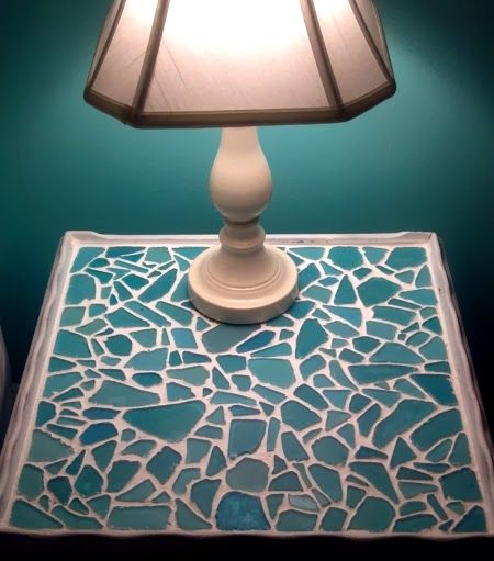 An old table was made over with a sea glass mosaic. The table top was spray-painted white first, then sea glass pieces were
