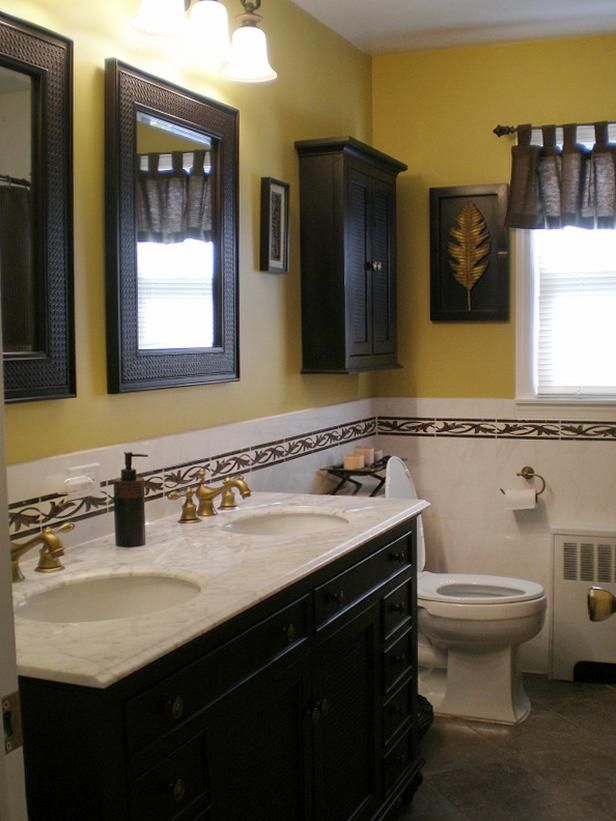 A Dark Free Standing Vanity Accented With Rattan And Accessorized With Tropical Inspired Artwork