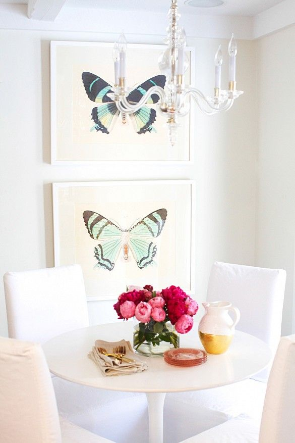 White dining space with butterfly artwork on the wall and crystal chandelier