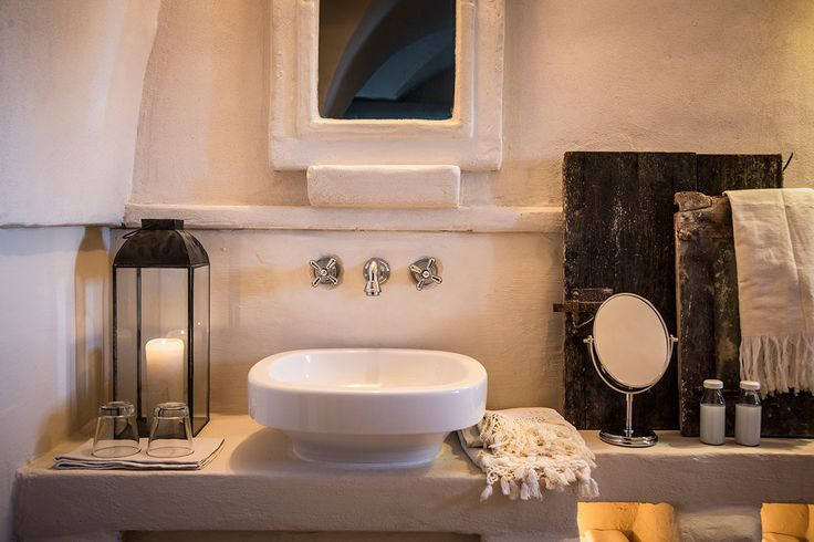 Bathroom at Masseria Le Carrube in Puglia, Italy with vessel sink, wall mounted taps and stucco walls