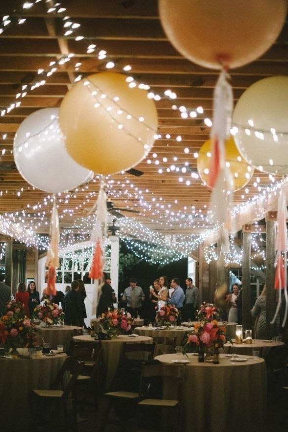 Love this whimsical wedding reception decor look with giant balloons and twinkly lights!: