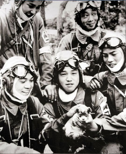 Kamikaze pilots playing with a puppy before their flights, May 1945: