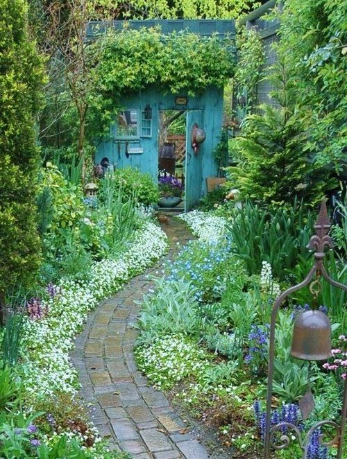 Freddy Moran-style house at the end of a strip-pieced path, with fussy-cut flowers to fill in the backgrou