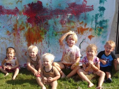 A white sheet and spray bottles with diluted paint = toddler fun & art all in on