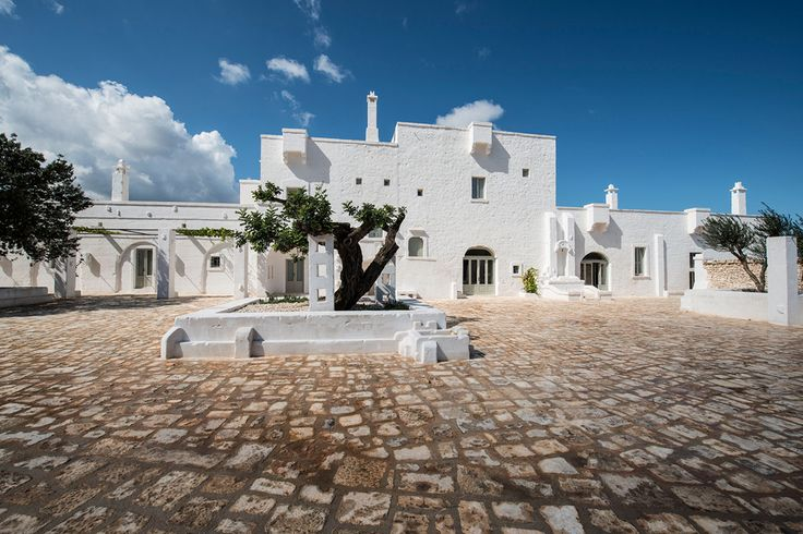 Exterior shot of Masseria Le Carrube in Puglia, Italy with blue sky and cobblestone driveway