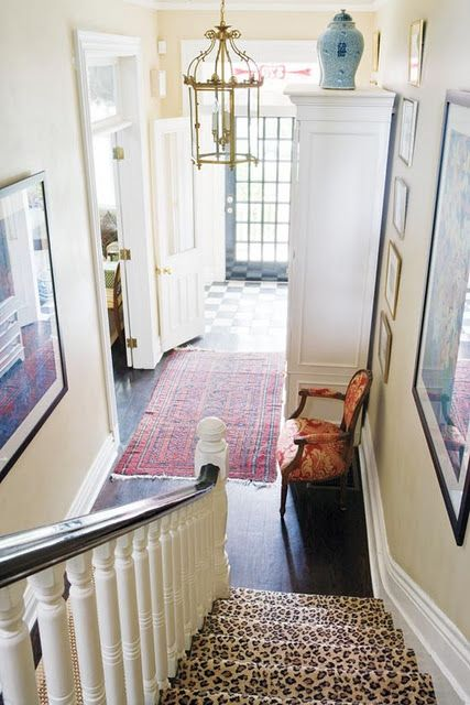 This entry way is warm and inviting. The checkerboard floor and door are gorgeous. I particularly love the red rug and the