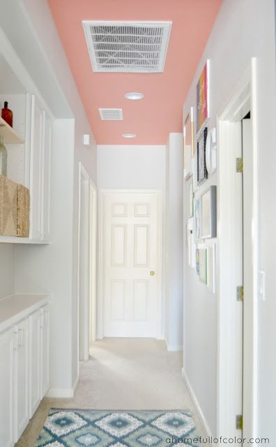 Want to keep a hallway white without it looking too sterile? Consider only painting the ceiling! Behr Youthful Coral ceiling with Behr Dolphin Fin walls