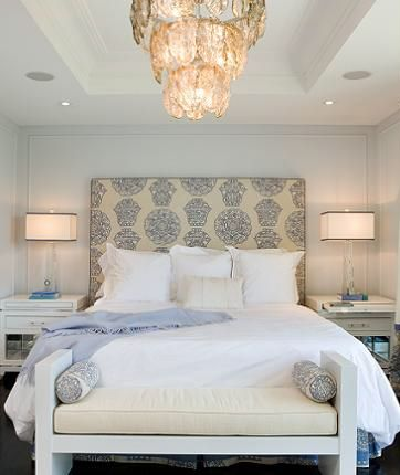 A gorgeous blue and white master bedroom. The focal point is the upholstered hea