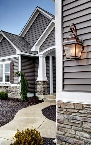 Love the colors, stone & oil bronzed light fixtures with the pops of white trim. Just love. And the black mulch is a great
