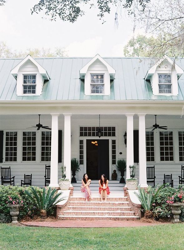 two girls sitting on front porch of plantation home http