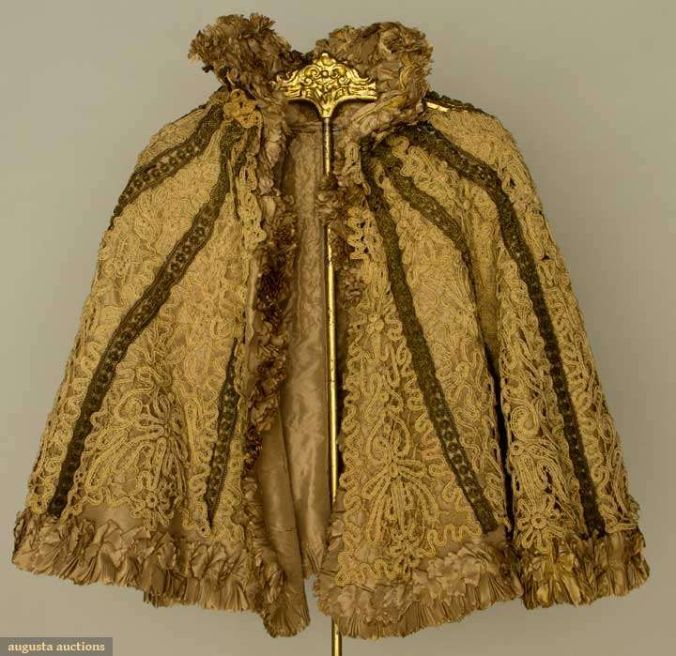 "Augusta Auctions, April 17, 2013 - NYC, Lot 209: ""Battenburg Lace Capelet"", 1890s Tape lace capelet, high stand collar, gold bullion trim, silk lining (damaged) very good.:"