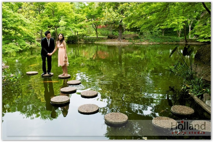 Engaged couple on the stones in the reflecting pool at the