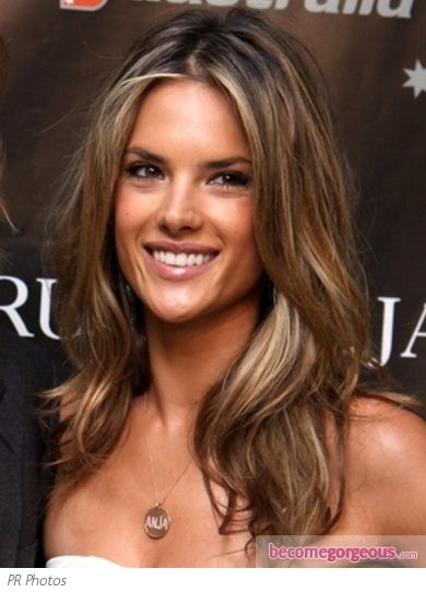 Iridescent golden highlights lift and add life to Alessandra Ambrosio base color. Her long layered locks appear more shiny and