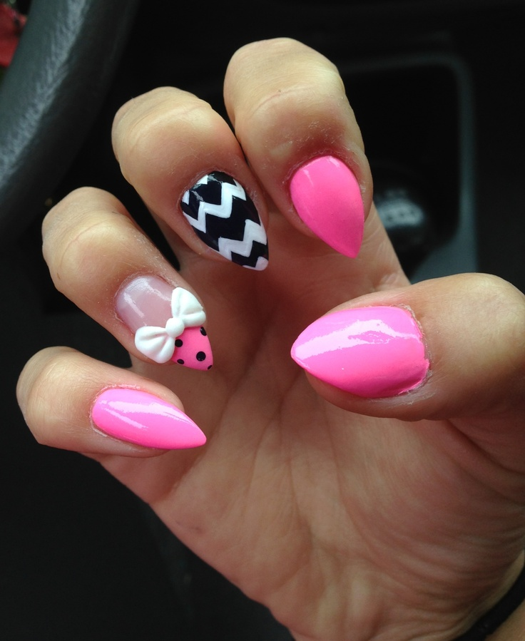 Short, pink, stiletto nails with a 3D acrylic bow and jem