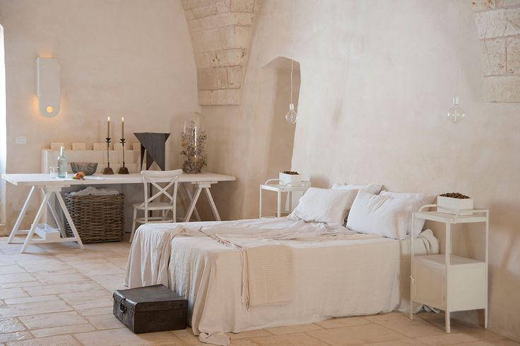 Bedroom at Masseria Le Carrube in Puglia, Italy with white linens and stucco walls