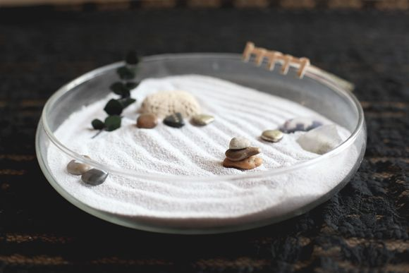 Mini Zen garden for stress relief at your desk. A shallow bowl, some sand, a few cool pebbles and trinkets, and a mini rake made from coffee stirrers.: