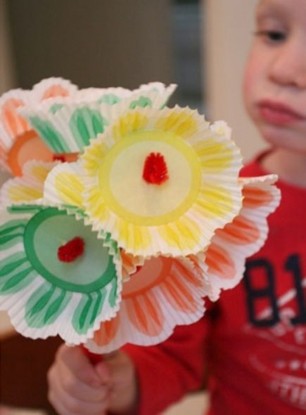 A child holding a bouquet of flowers made of cupcake liners