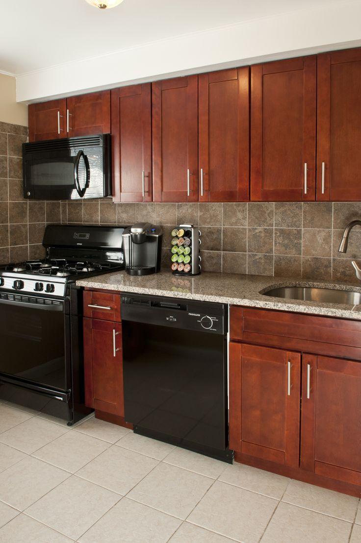 Cherry granite countertops, black appliances