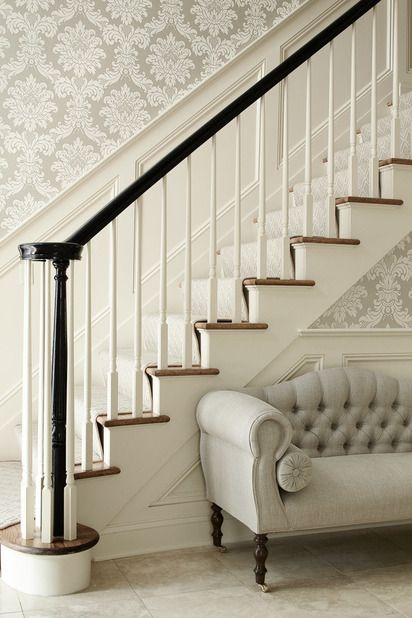 Elegant foyer with silver gray damask wallpaper, wainscoted staircase, glossy black banister and gray tufted settee with caster