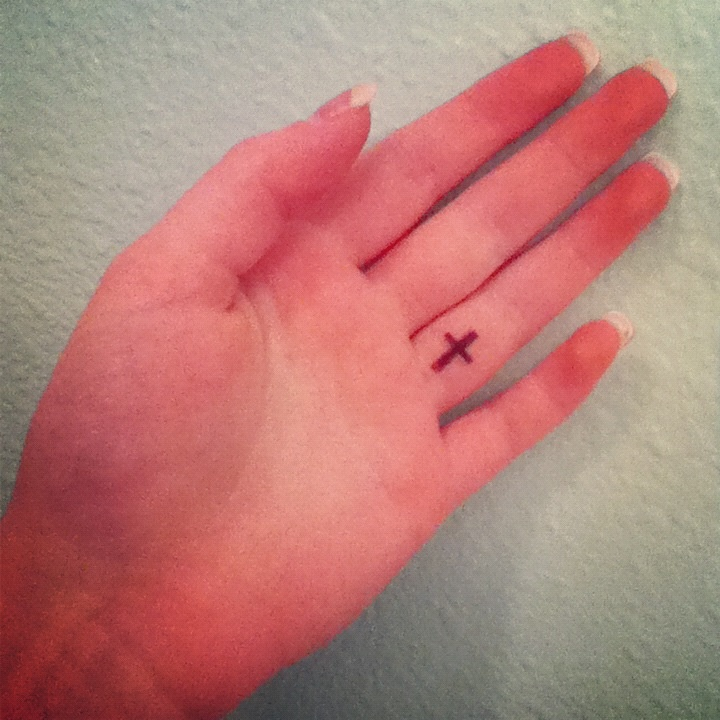 Small cross tattoo perfect placing on the left ring finger