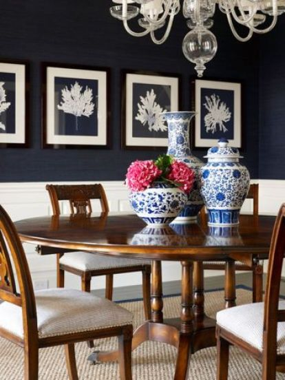 Crisp white wainscoting, navy blue walls provide perfect backdrop for traditional dining table with lovely blue & white china arrangement. Note the small, med, large placement of the china! Designed by Allison Caccoma and featured on Domino.com