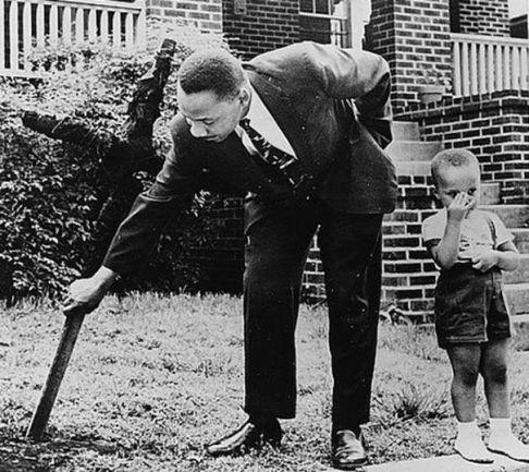 Martin Luther King e seu filho removendo uma cruz queimada do seu quintal, 1960: