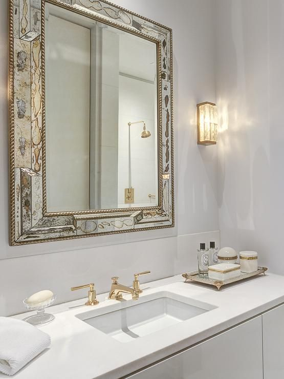 White And Gold Bathroom Features An Antiqued Mirror