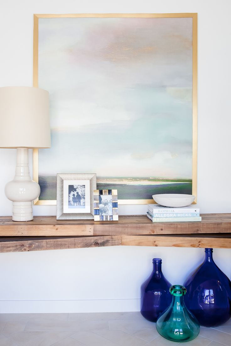 Alice Lane Home Collection | Solameer Townhome | Entry with landscape artwork, cream lamp, and blue accent
