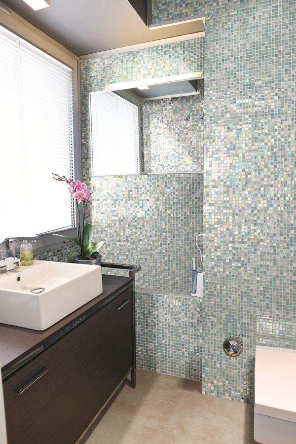 Love a shimmery mosaic tile floor to ceiling in a bathroom!