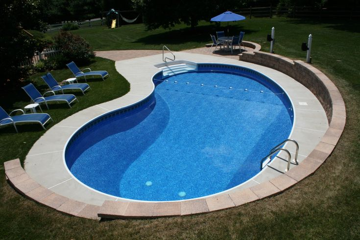 A Kidney Shaped Pool With Brushed Concrete Decking And A