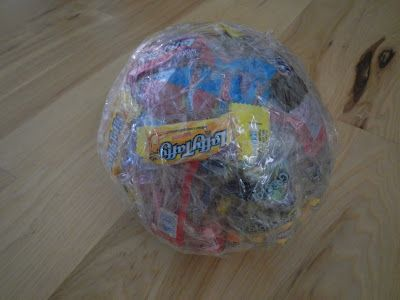 The idea is to use saran wrap & tape to create a ball. As you continue to wrap you add a piece of candy to each layer. Have the