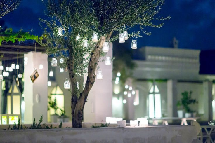 Exterior shot of Masseria Le Carrube in Puglia, Italy in the evening with candle lanterns hung from trees