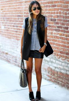 Jules Sarinana of Sincerely Jules in a leather skirt, graphic tee, black vest, and mules
