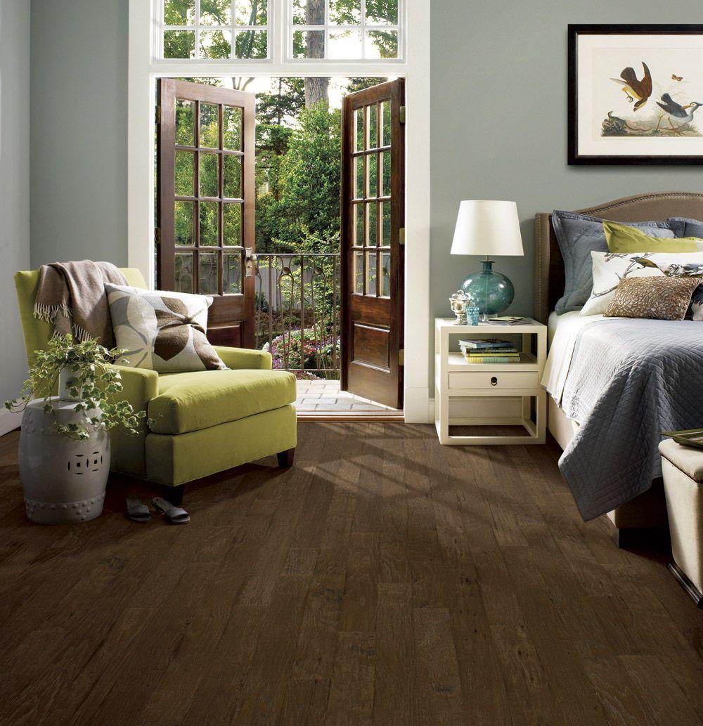 Light grey walls with dark wood floor in bedroom with