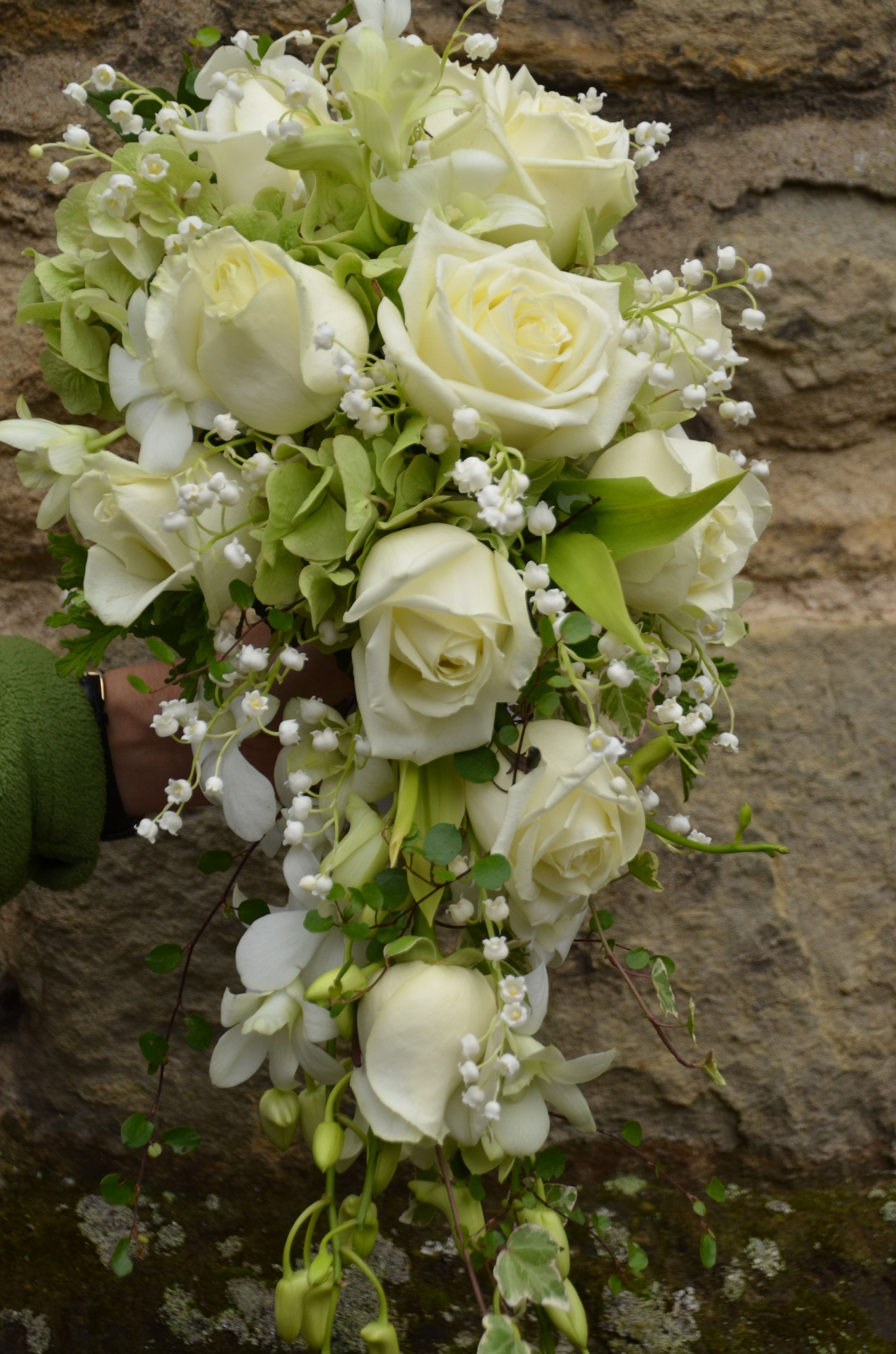 tailing shower bouquet of roses and lily of the valley