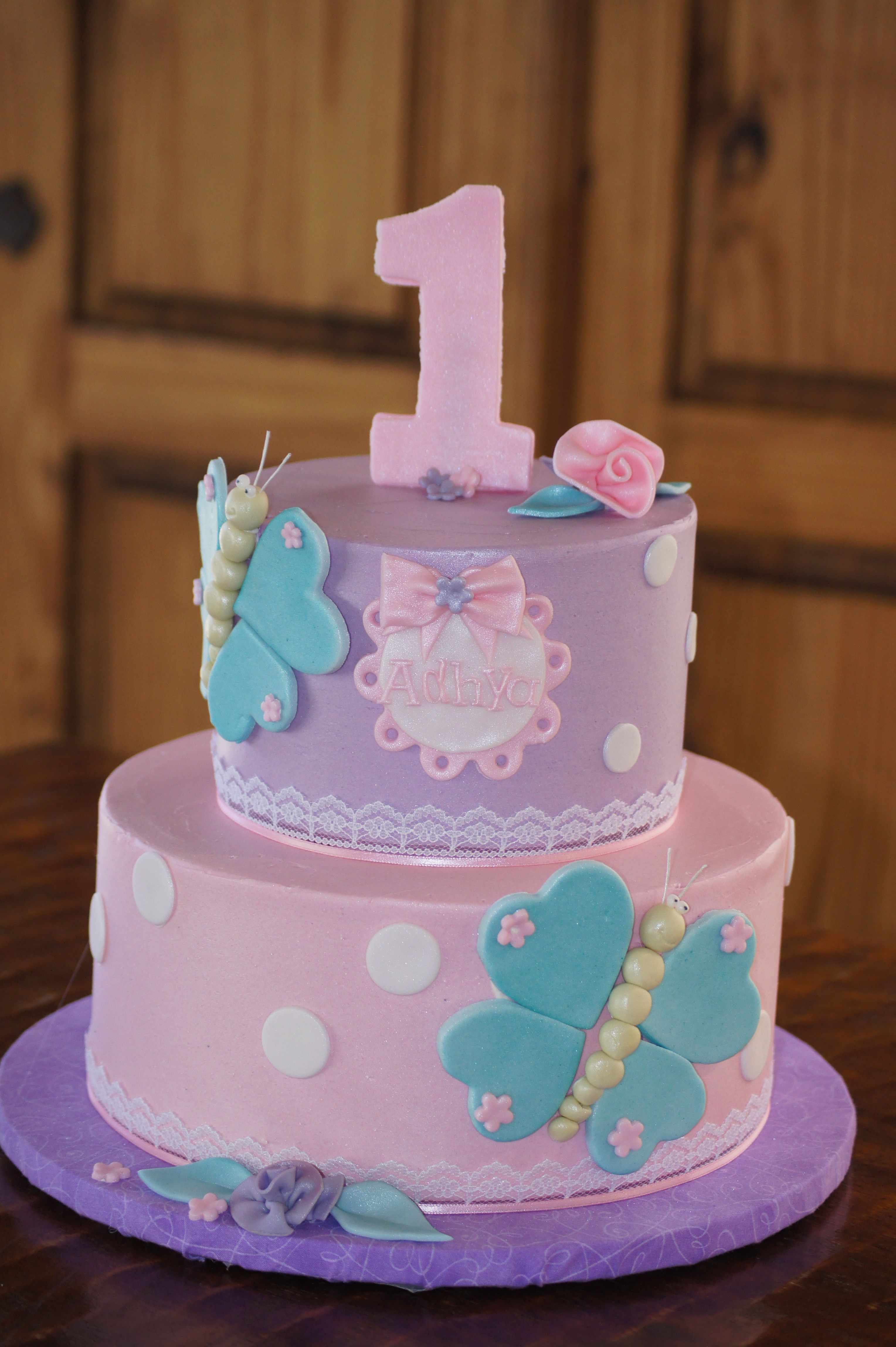 Tiered pink and purple butterfly cake with white polka