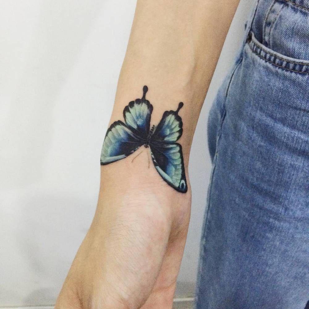 Blue butterfly tattoo on the right wrist. Tattoo artist