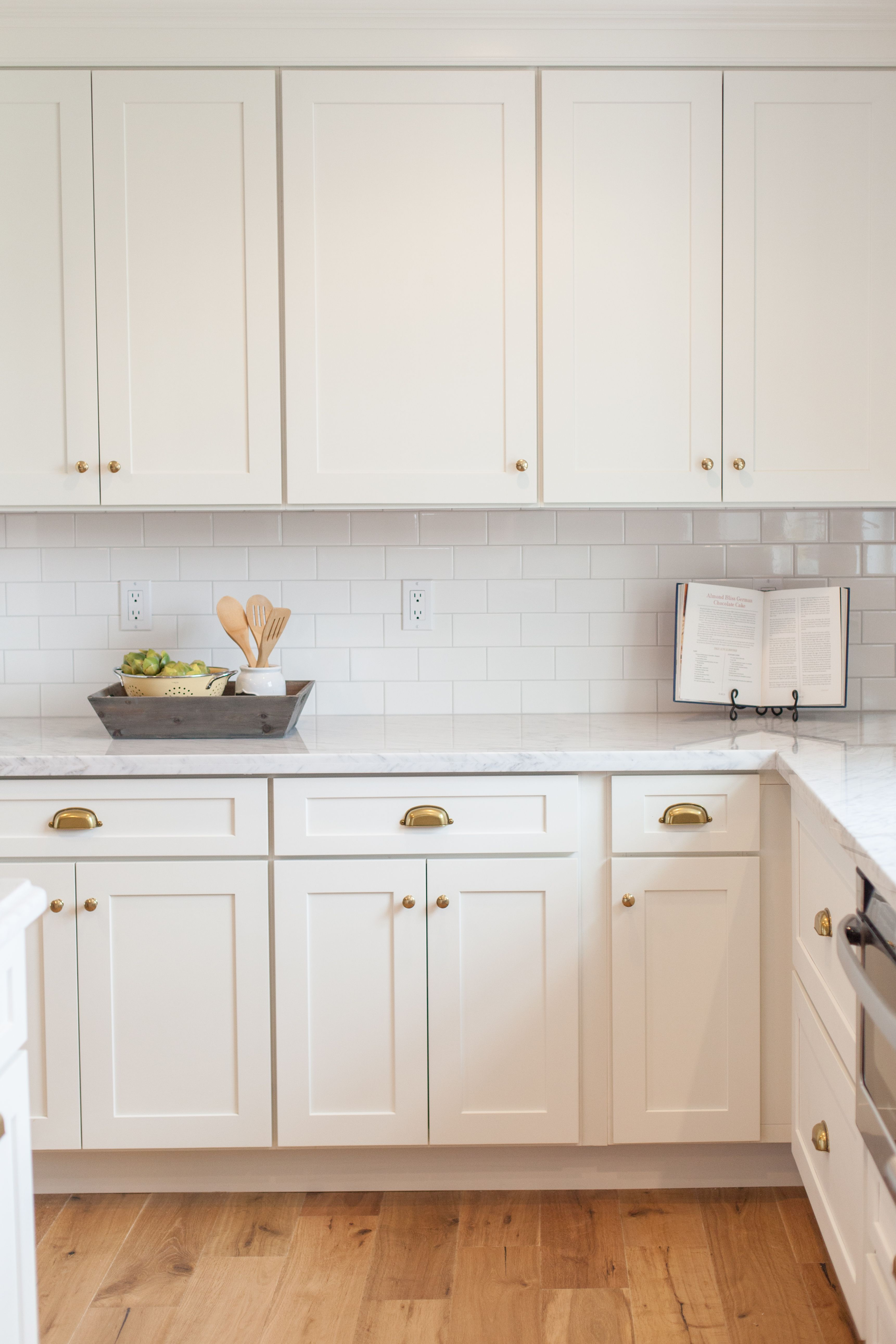 White shaker with brass cups and knobs by
