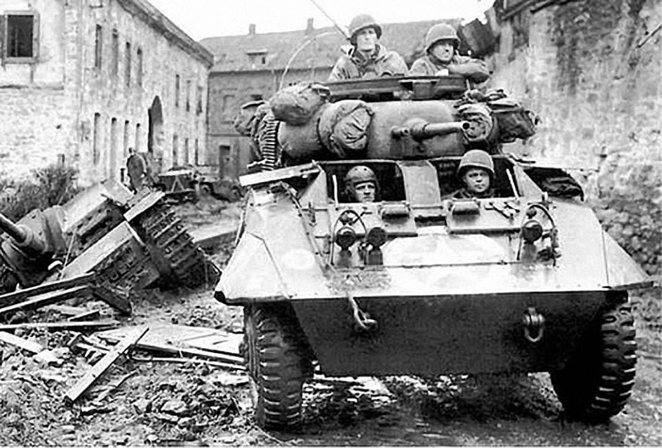 M8 Greyhound from 30th Infantry Division moves out from