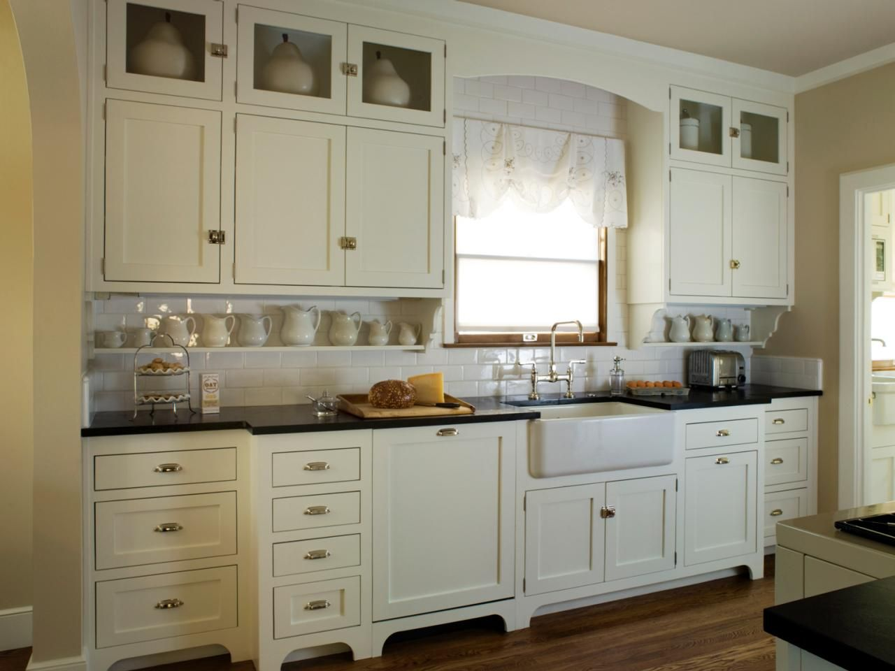 This quaint cottage kitchen features antique white Shaker